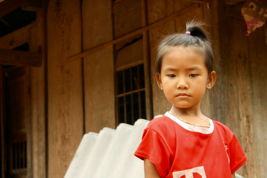 Image of a young girl with a bit of attitude watching us work in Xom Pung Village Vietnam.