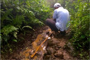 Image of my guide on the hike up Volcano Maderas in Nicaragua chopping a walking stick for me.