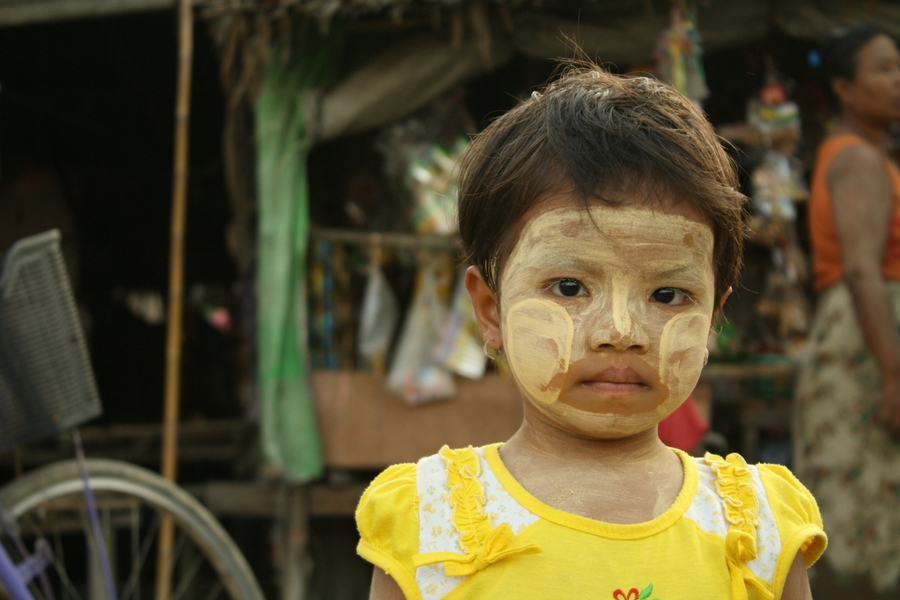 A young girl with thanaka on her face tentatively watch us pass out rice in her village near Yangon.