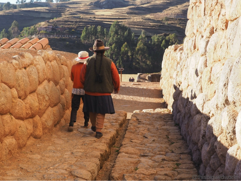 Image of a Peruvian couple walking along the stone path in front of the church at Chinchero in the Sacred Valley near Cusco Peru.