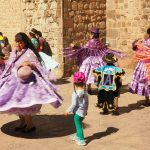 Image of women dressed in colorful outfits dancing in the streets of Cusco for the Corpus of San Cristobal festival in Cusco Peru.