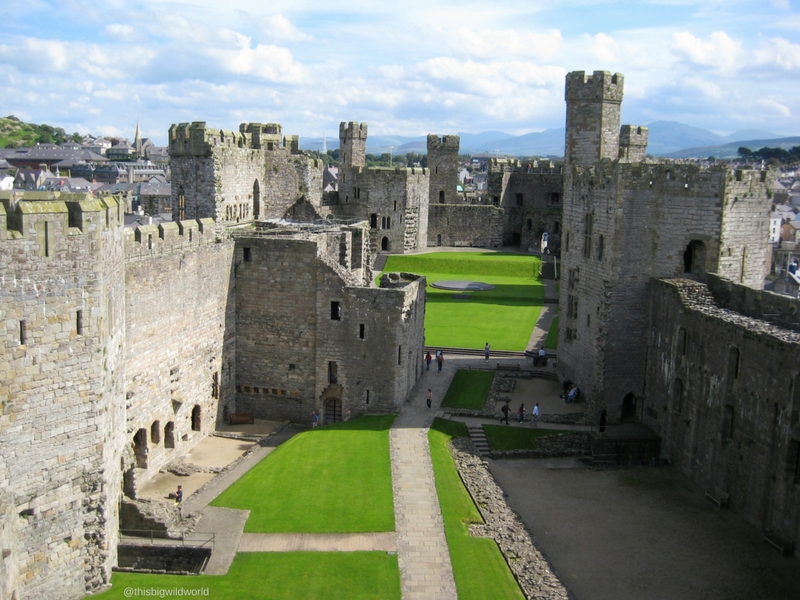 Image of the inside of Caernarfon Castle and the city of Caernarfon beyond it in North Wales.