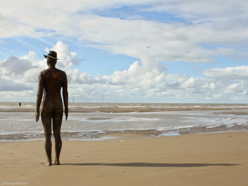 Image of Antony Gormley statue silhouette installed at Crosby Beach near Liverpool in England.