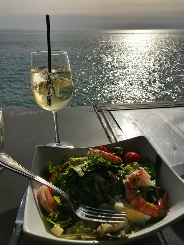Image of cocktail and salad looking out at the ocean from Moonshadows restaurant in Malibu California.