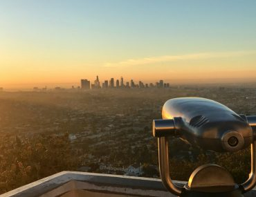 Image of downtown LA from Griffith Observatory at Sunrise in LA. The sky is bright pink and yellow.