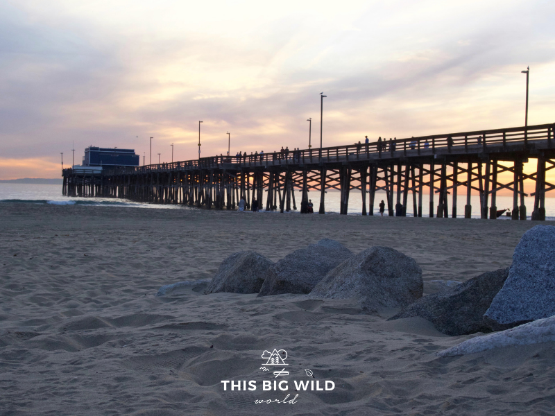 Image of a bright pink and blue sky as the sun set behind Newport Beach pier in California.