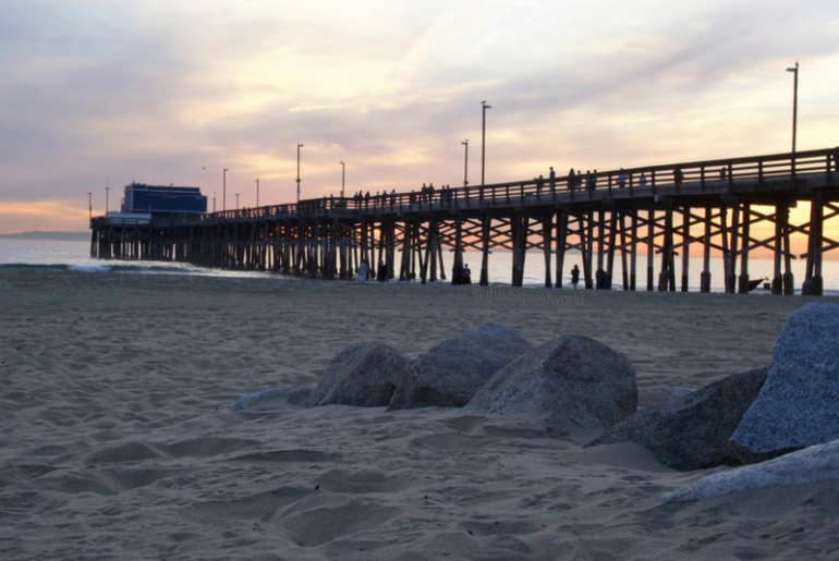 Image of a bright pink and blue sky at sunset behind the Newport Beach Pier in Orange County California.