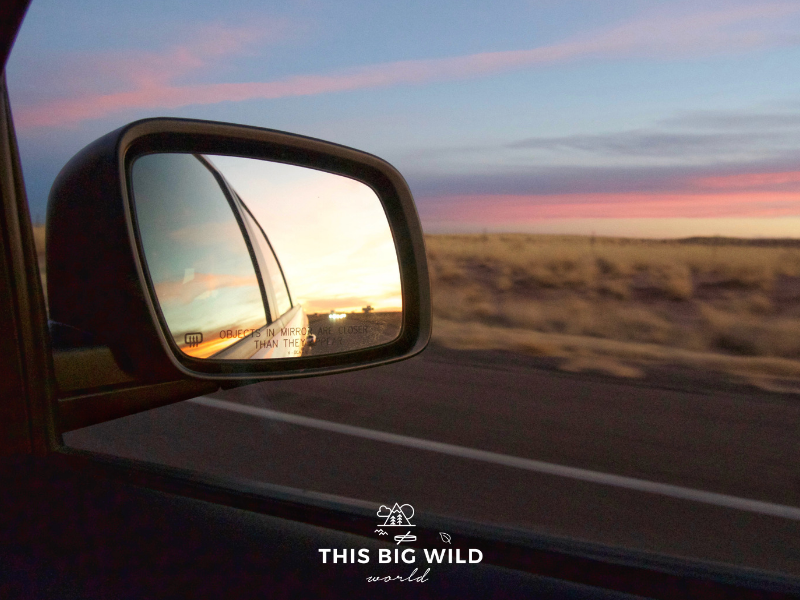 Image of rearview mirror with colorful pink and blue sunset as we drove through Arizona on our Los Angeles to Denver road trip.