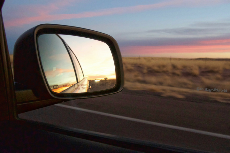 Image of rearview mirror with colorful pink and blue sunset as we drove through Arizona.