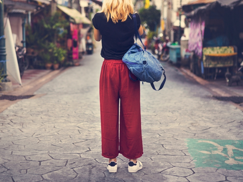 Woman standing alone at a local market wishing she had a travel companion.
