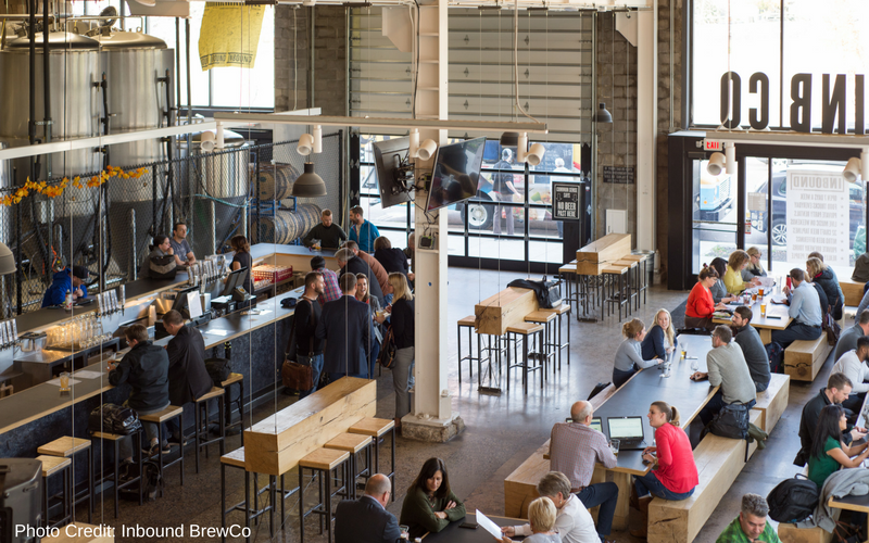 Inbound BrewCo is one of the best Minneapolis breweries, located in the North Loop neighborhood near Target Field. Chunky wood tables and benches filled with people, the metal bar is an island int he center of the space with large metal brewing equipment in the background. The room is lined with windows and doors that open up to the outside.
