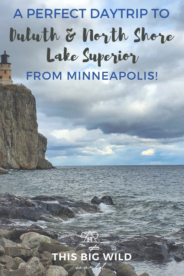 Text: A perfect daytrip to Duluth & North Shore Lake Superior from Minneapolis! Image: On the left is tall and rugged granite rock with a pale peach lighthouse on it. The lighthouse looks out onto dark blue water below, with a rocky shoreline in the foreground. Above is a cloudy sky. This is Split Rock Lighthouse in Minnesota.