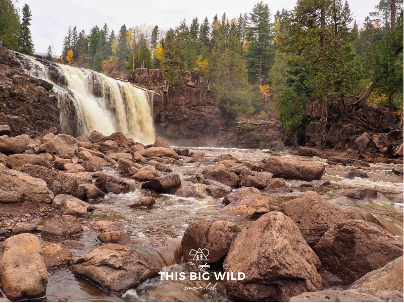 To the left in the distance is a tall waterfall lined on either side with yellow and green pine trees. In the foreground, the water flows over large rocks at Gooseberry Falls State Park along Minnesota's North Shore of Lake Superior.