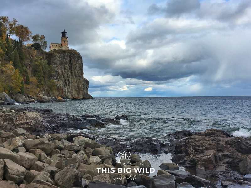 From the left is a granite rock formation with a peach lighthouse, overlooking the dark water of Lake Superior. In the foreground is a rocky beach and in the distance to the right is a peek at a blue sky through the dark stormy clouds at Split Rock Lighthouse State Park along Lake Superior in Minnesota.