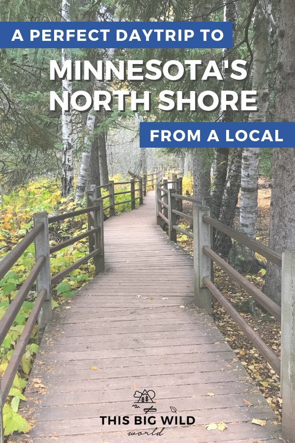 Text: A perfect daytrip to Minnesota's North Shore from a local. Image: A crooked wooden boardwalk with handrails on either side goes down the center of the image. On either side are trees, bright green brush and a hint of yellow fall colors at Gooseberry Falls State Park in Minnesota.