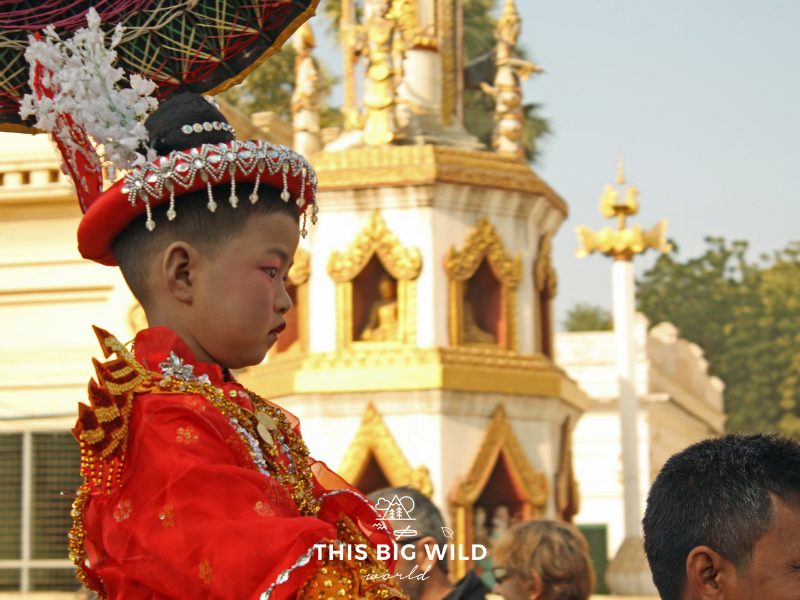 Image of a young boy dressed in opulent clothing in a Shinbyu Parade near Bagan Myanmar. After the parade he will leave his family to become a novice monk.