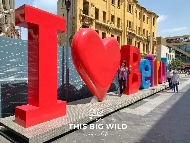 "Me standing with a large brightly colored sign that says ""I Love Beirut"" located at the Beirut Souk."