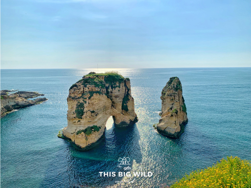The lightly colored Corniche rock formation standing tall in the bright blue water just before sunset in the Raouche neighborhood of Beirut.