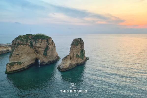 Pink and blue sky behind the Corniche rock formation at sunset in Beirut.