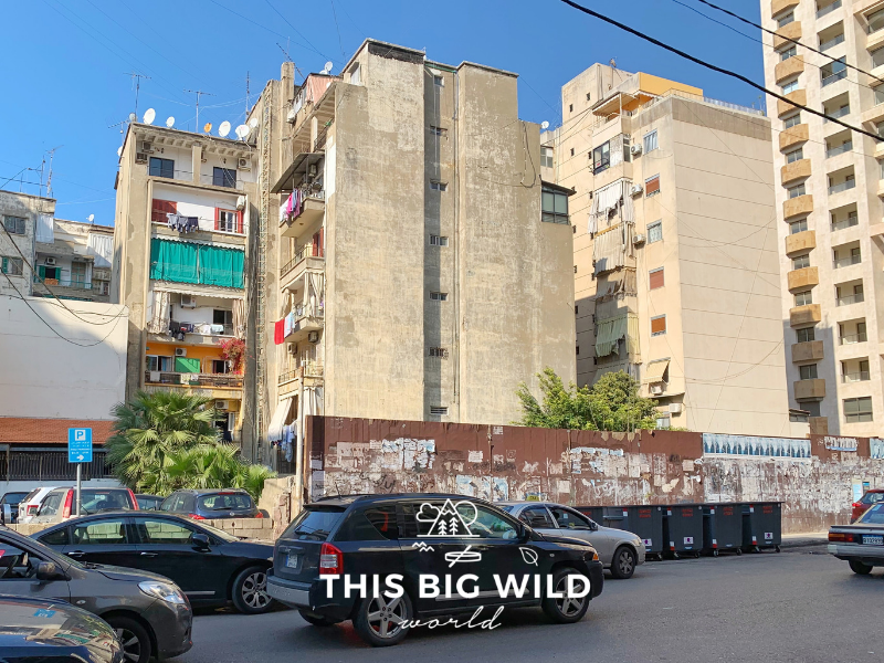 Cars drive by in the Hamra neighborhood of Beirut. Apartment buildings and shops line the streets.