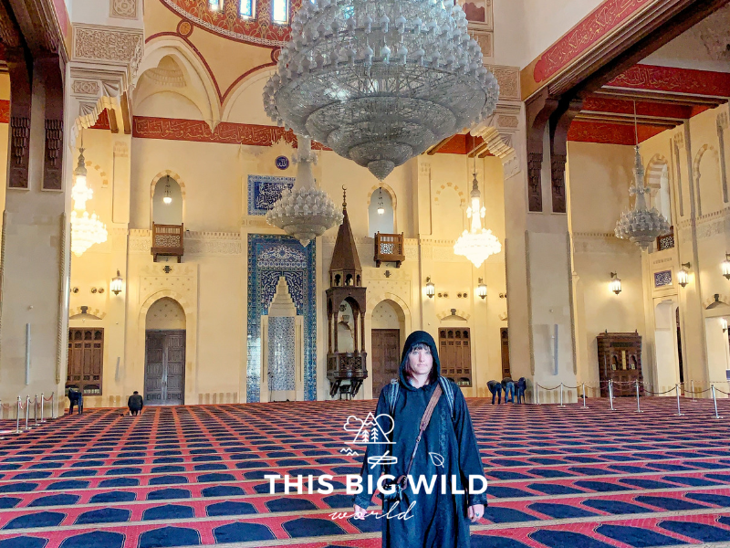 Me wearing a black cloak and head covering inside Mohammed Al Amin mosque in Beirut. Extravagant crystal light fixtures hang from the ceiling over the prayer space.