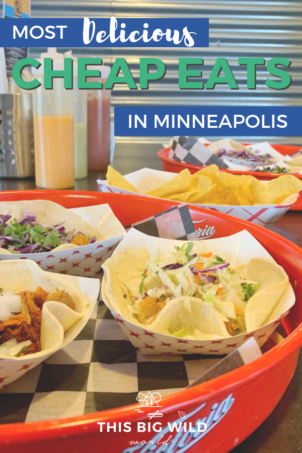Text: Most Delicious Cheap Eats in Minneapolis Image: Close up of red tray with three separate paper trays each with a soft taco. In the background is a tray of tortilla chips, more tacos and clear bottles of hot sauce.
