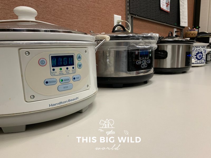 Crockpots of all types lined up on a table for a potluck dinner in Minnesota.