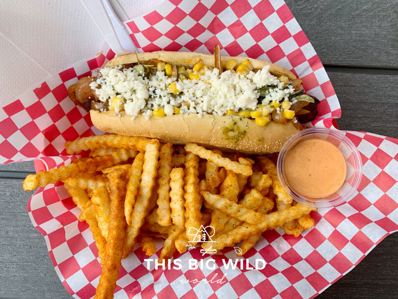 The Phoenix hot dog is wrapped in bacon and topped with corn, poblanos, and crema with a side of smokey chili fries from International House of Hotdogs in Anchorage.