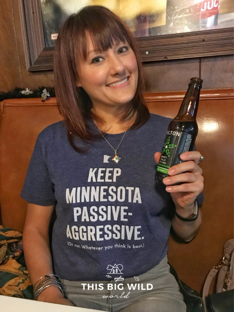 "My shirt reads ""Keep Minnesota passive aggressive. (Or not, whatever you think is best.)"" and I'm drinking local beer from Fulton brewery."