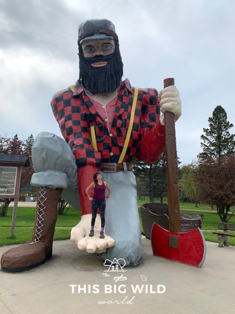 Standing in the hand of a statue of Paul Bunyan in Akeley Minnesota. The statue is more than 25 feet tall and is one of many Paul Bunyan statues throughout Minnesota.