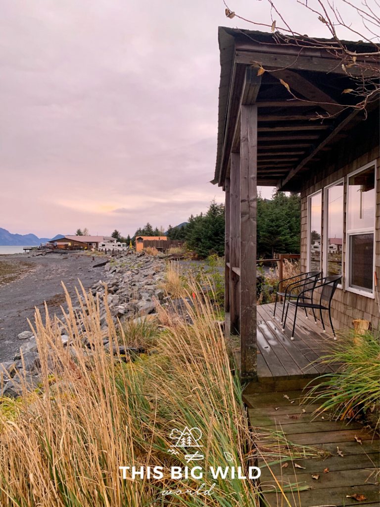 A small cabin with a patio right on the water at Resurrection Bay. The sky is a light pink color with another cabin off in the distance.
