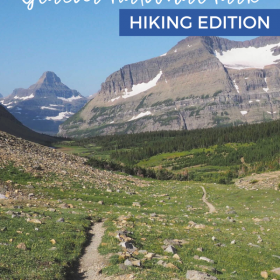 Text: What to pack for Glacier National Park - Hiking Edition Image: A narrow hiking trail extends off into the distance where there are snow covered mountains.
