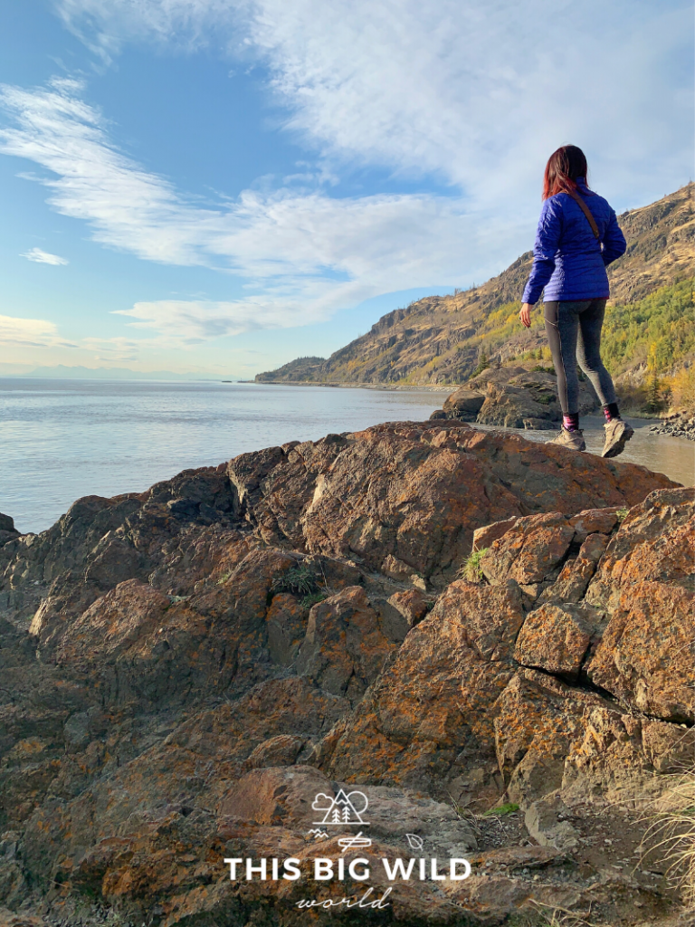 Me standing on a large rock overlooking Turnagain Arm with a rugged coastline behind me and bright blue sky above. The sun is low in the sky, creating a golden effect.