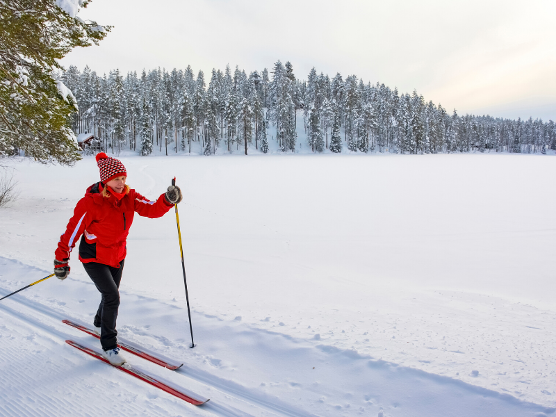 A woman cross-country skis in fresh white powdery snow with a snow covered treeline in the background.