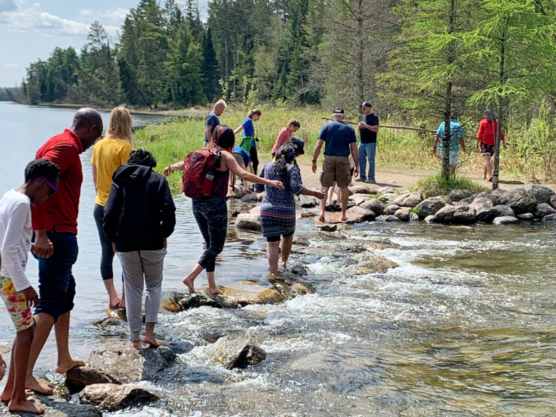 A group of people walks barefoot across a series of rocks as the headwaters of the Mississippi River flow in Itasca State Park in Minnesota. This is a must for any outdoor lover's Minnesota bucket list!
