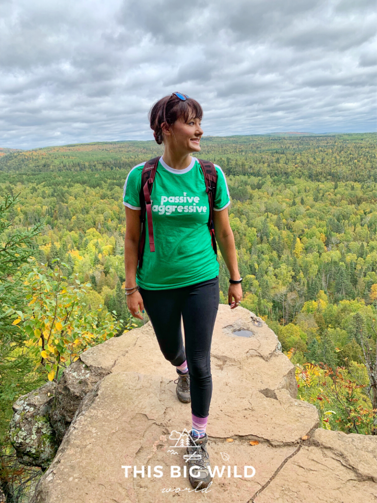 A woman in hiking gear standing on a rock overlooking miles of trees in bright fall colors in northern Minnesota.