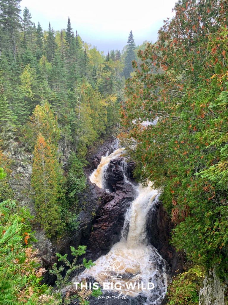 A series of waterfalls flows through dark rock which creates Devil's Kettle Falls in Judge CR Magney State Park in northern Minnesota. The fall colors are just beginning to change creating pops of orange and red in the lush green lining the waterfall. A must for any Minnesota bucket list!