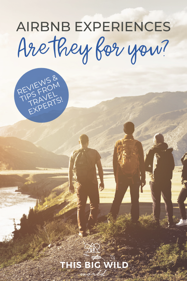 Text: Airbnb Experiences - Are they for you? Reviews & tips from travel experts! Image: Group of people with their backs to the camera looking at mountains in the distance from a hiking trail. The sun is low in sky off to the left of the frame.
