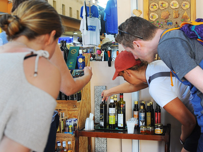 A group of people is hunched over looking at a display of different types of olive oil just before they begin their olive oil tasting. This Airbnb Experience is hosted by Gabi from The Tiny Book in Crete, Greece. Photo credit: The Tiny Book