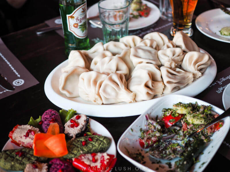 A spread of traditional Georgian foods, including dumplings called Khinkali, on a dark wood table. This was just one stop on Emily's food tour in Tbilisi Georgia. She shares more in this Airbnb Experiences review!