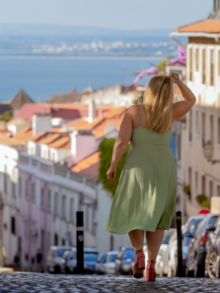 A woman in a pale green sun dress and red heels strolls the colorful streets of Lisbon Portugal on a sunny day during her photography tour with Airbnb Experiences. Photo provide by: Destination: Live Life.
