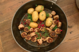 Finnish meatballs and dill potatoes with lingonberries in a metal skillet over a wooden table. Prepared during an Airbnb Experiences cooking class in Helsinki Finland.