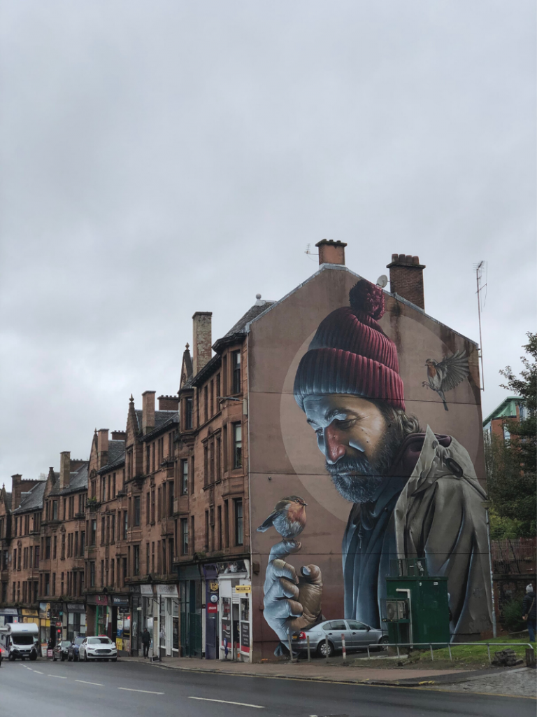 A row of flats in Glasgow is lined with shops on the ground floor on a gray cloudy day. On the end of the building is a large painting of a man in winter hat holding a small bird in his hand. This is one of many stops on a Street Art tour in Glasgow with Airbnb Experiences. Photo credit: Laura No Esta