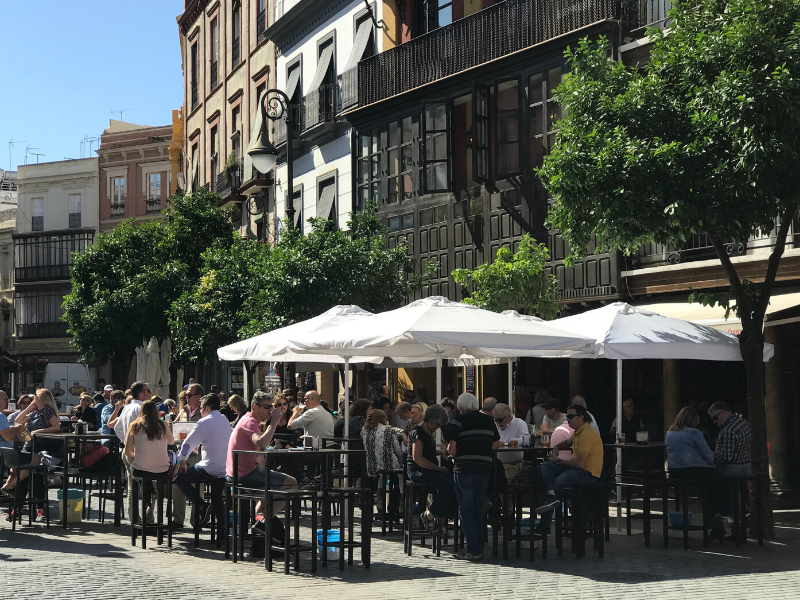 Lining the sidewalk in front of a row of old colorful buildings in Seville, are tables filled with locals enjoying tapas and drinks on a sunny day. Photo credit: Where Angie Wanders