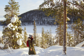 How to choose between Levi and Rovaniemi when visiting Lapland in winter! Image of me hiking in deep snow in a forest overlooking a frozen lake with sun shining on me.