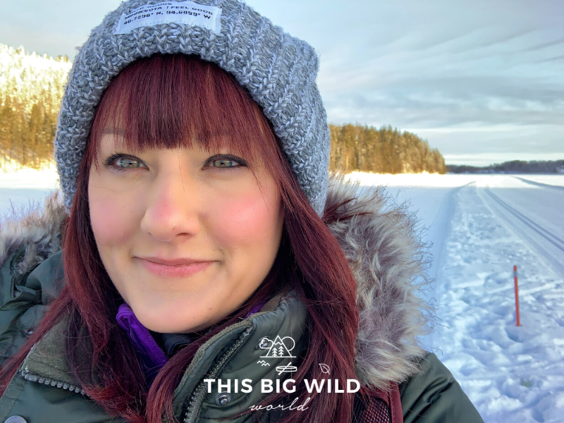 Close up shot of me, a woman with bright red hair, a gray winter hat and green puffy coat with a fur around the hood. Behind me is a frozen lake with sun hitting a the snow covered fell lined with pine and fir trees.