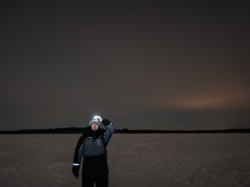 Standing on a frozen lake in the dark with a cloudy sky behind me. I'm wearing a lit headlamp as I look up at the sky.