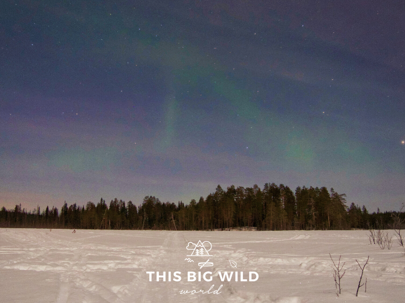 A faint view of the Aurora Borealis in the sky outside of Rovaniemi as seen from a frozen lake.