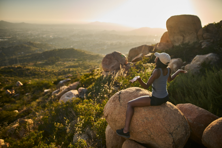 Hiker sits on rock overlooking green valley at sunset.