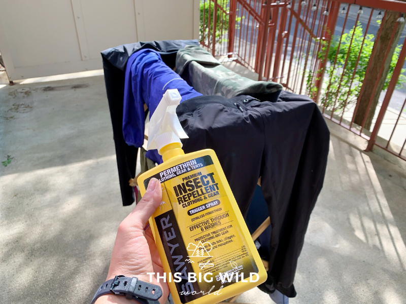 Yellow spray bottle of Sawyer permethrin spray in front of a rack of clothes outside on a patio.
